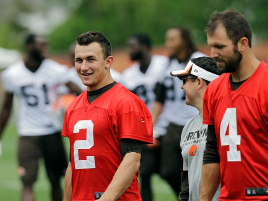 Cleveland Browns quarterback Johnny Manziel (2) walks off the field with Tyler Thigpen (4) and quarterbacks coach Dowell Loggains after a mandatory minicamp practice at the NFL football team's facility in Berea, Ohio Thursday, June 12, 2014.  (AP Photo/Mark Duncan)