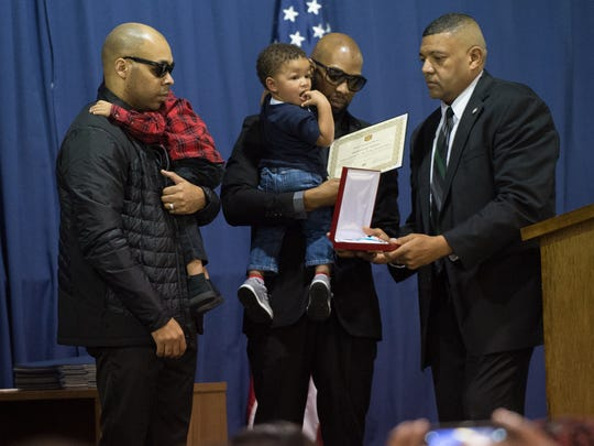 Delaware Correctional Commissioner, Perry Phelps, right, makes a presentation to family members of Sergeant Steven R. Floyd, at the Correctional Employee Initial Training graduation ceremony in Dover.