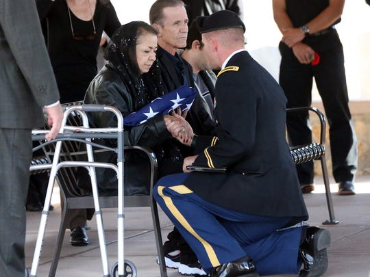Alicia Schultz receives the folded flag of her father, Sgt. Alexander Ruiz Martinez, at Fort Bliss National Cemetery on Monday. Next to her is her husband, Oscar Schultz.