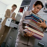 Businesswoman carrying a stack of documents is shown in this undated photo.