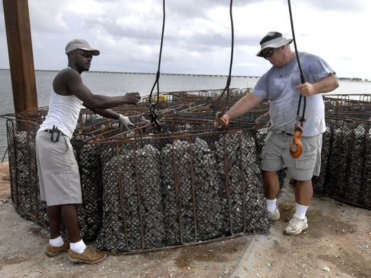 Willie Fountain, left, and Bill Carson hook up an oyster