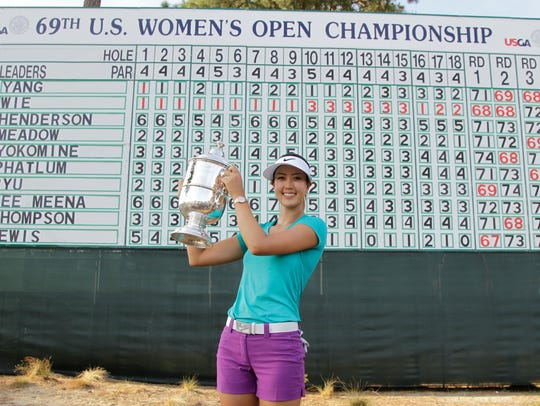Michelle Wie pass with the trophy after winning the