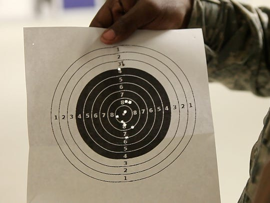 Marquis Smith holds up his target at the Junior ROTC shooting range at the Leadership Academy for Young Men at Charlotte. Smith is a senior who hopes to join the military after graduating from high school this year.