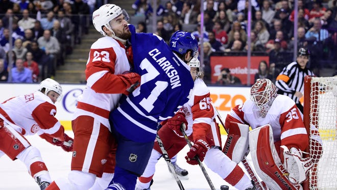 Detroit Red Wings' Brian Lashoff (23) hits Toronto Maple Leafs' David Clarkson (71) as he tries to get a shot on net during the second period Saturday. Toronto won 4-1.