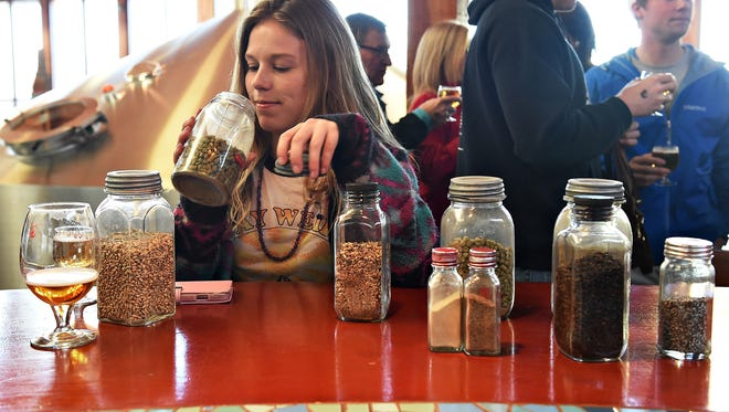 Cari Heroux smells a jar of hops during a tour of New Belgium Brewing Company on Friday, February 12, 2016.
