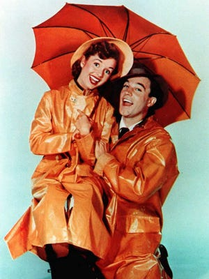 """Debbie Reynolds, then 19, poses with Gene Kelly in a publicity still from """"Singin' in the Rain."""""""