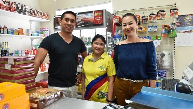John B's Mart store co-owners Mark Redila, left, and Rubyjane Buhain-Redila, right, pose for a photo with their cashier Nenita T. Yanson, center, at John B's Mart in Tamuning on Feb. 1, 2017.