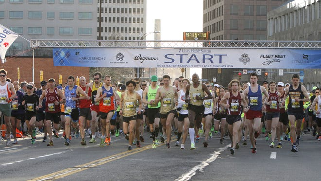 Runners take off at the start of the annual Flower City Challenge half marathon road race Sunday, April 28, 2013.