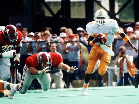 Tennessee quarterback Tony Robinson  gets  away from Alabama defenders Jon Hand (78) and Curt Jarvis (95) on Oct. 19, 1985.