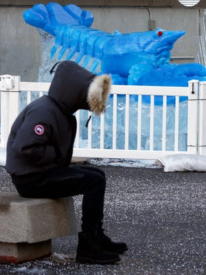A person sits bundled against the cold near a blue lobster ice sculpture, Thursday, Dec. 28, 2017, outside the New England Aquarium in Boston. The National Weather Service said there's the potential for record-breaking cold this week in New England.
