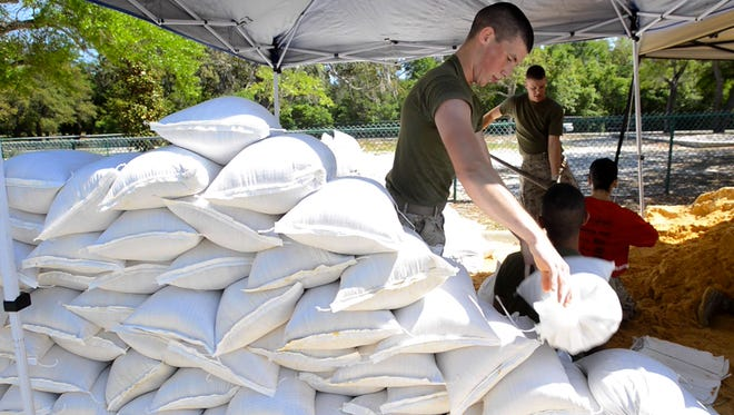 PFC Dean Pullman and others from Marine Aviation Training Support Group 21 fill sand bags at the Gulf Breeze Community Center on Thursday as residents prepare for more rain and possible flooding.
