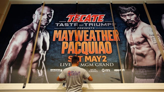 Jose Arroyo installs an advertisement for a fight between Floyd Mayweather Jr. and Manny Pacquiao at the MGM Grand, Friday, April 24, 2015, in Las Vegas. The fight is scheduled to take place May 2 at the hotel and casino. (AP Photo/John Locher)
