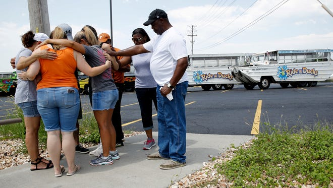 People pray Friday outside Ride the Ducks, an amphibious tour operator involved in a boating accident on Table Rock Lake in Branson, Mo.