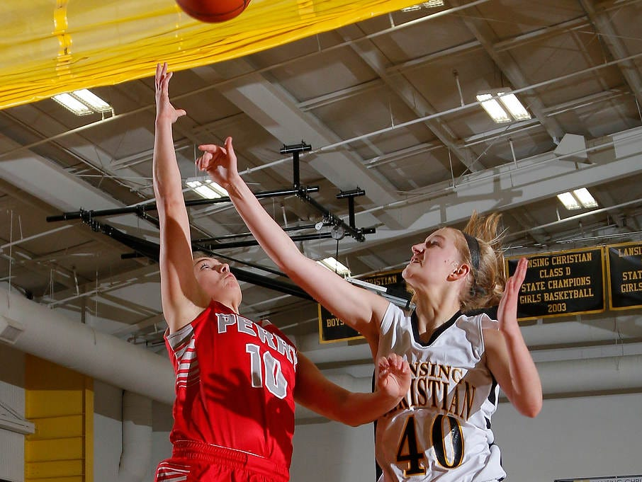 Perry's Abigail Dollar, left, gets a fast-break layup against Lansing Christian's Grace Haley (10) Friday, Feb. 13, 2015, at Lansing Christian School. Perry won 62-28.