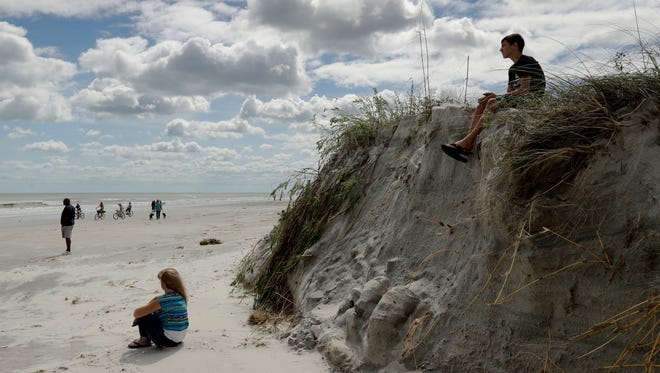 A boy sits on a cliff formed by erosion from Hurricane Matthew on the beach at Jacksonville Beach, Fla. Saturday, Oct. 8, 2016. The fast-weakening storm continued its march along the Atlantic coast Saturday.