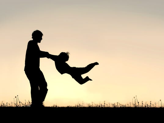 Silhouette of Father Spinning CHild Around Outside