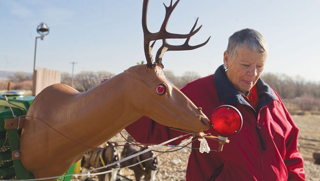 """In this Dec. 13, 2017 photo, Lynn Hiatt touches the """"Rudolph"""" head fixed to the front of a tractor that sits in front of the home she shares with her husband, Dale, off of Snowy Range Road in Laramie, Wyo."""
