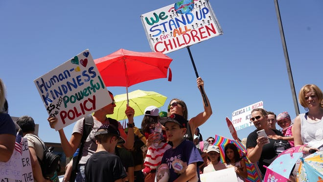 Protesters from both sides of the immigration debate rally outside the offices of Sens. John McCain and Jeff Flake in Phoenix on June 20, 2018.