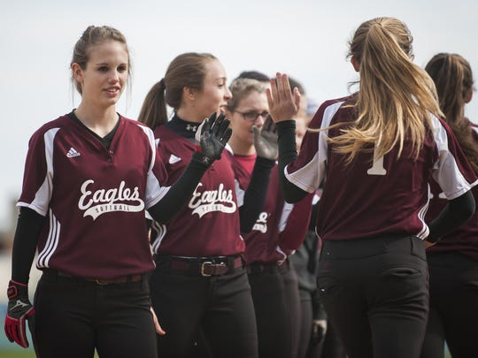 The Mount Abraham high five each other during player introductions during the high school girls softball game between the Mount Abraham Eagles and the Essex Hornets at Essex high school on Thursday afternoon.