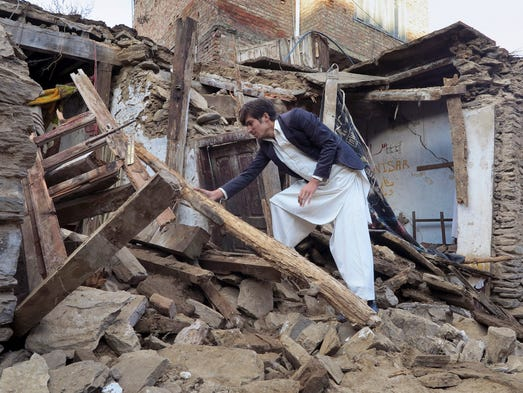 A Pakistani boy examines a house damaged by the massive