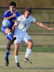 Luke Brougham of Memorial battles with Jason Cherry of Bloomington South during the first half of the Boys 2A regional at Jasper High School Thursday.  Memorial won on penalty kicks to advance.