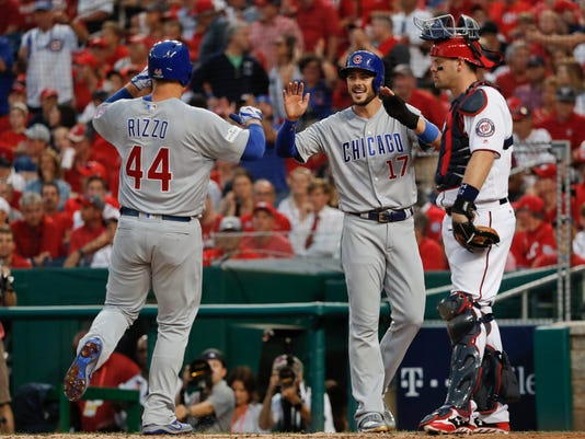 Chicago Cubs' Anthony Rizzo (44) is greeted at home by teammate Kris Bryant (17) after Rizzo hit a two-run home run off Washington Nationals starting pitcher Gio Gonzalez in the fourth inning in Game 2 of baseball's National League Division Series, at Nationals Park, Saturday, Oct. 7, 2017, in Washington. Watching is Washington Nationals catcher Matt Wieters. (AP Photo/Pablo Martinez Monsivais)