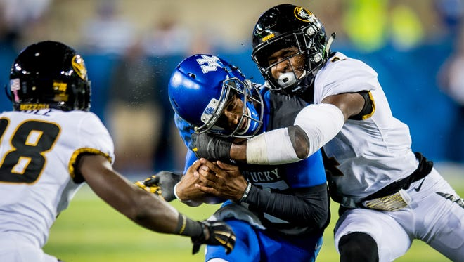 Kentucky Wildcats quarterback Stephen Johnson (15) is tackled by several Missouri Tiger defenders during the game at Kroger Field on the campus of the University of Kentucky in Lexington, Saturday, Oct. 7, 2017.