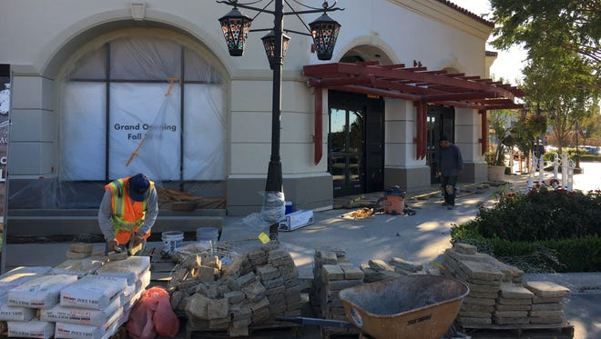 In a Sept. 24 photo, workers are seen installing cobblestones at the front entrance to Vintage Grocers, which will open Oct. 1 at the former Bristol Farms site in the Promenade at Westlake in Thousand Oaks.