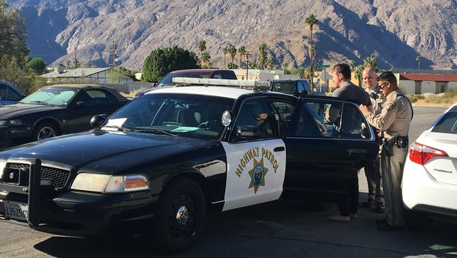 California Highway Patrol officials take an auto theft suspect into custody Tuesday during a raid on a Palm Springs home. The suspect was identified as Guilherme Oliviera, 27.