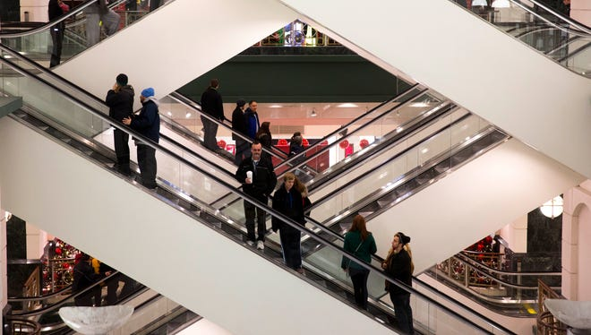 Shoppers ride escalators between floors during Black Friday 2013 shopping at Macy's, in Chicago.