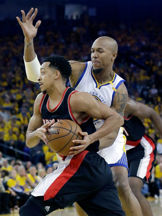 Portland Trail Blazers guard C.J. McCollum, left, drives against Golden State Warriors forward David West during the second half of Game 1 of a first-round NBA basketball playoff series in Oakland, Calif., Sunday, April 16, 2017. The Warriors won 121-109. (AP Photo/Jeff Chiu)