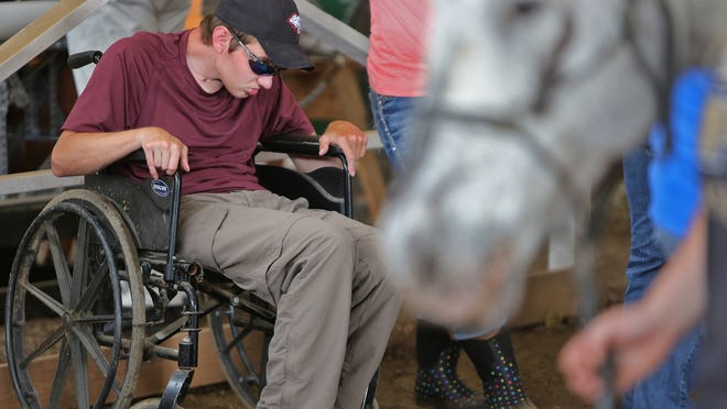 Former Rose-Hulman student Drew Christy, who was paralyzed in a car accident several years ago, joins others at Hope Haven Horse Farm, Tuesday, May 27, 2014.  For their senior projects, some Rose-Hulman biomedical engineering students worked on projects geared toward helping real people, like Christy.  Their client, Hope Haven Horse Farm, works with disabled people by doing therapeutic riding.