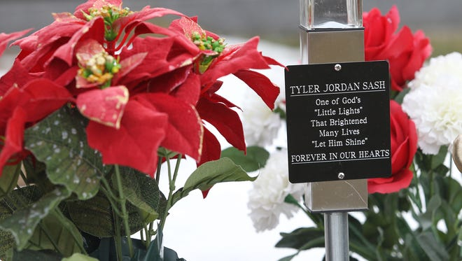 Flowers rest where Tyler Sash is buried at Forest Cemetery in Oskaloosa on Wednesday, Jan. 27, 2016.