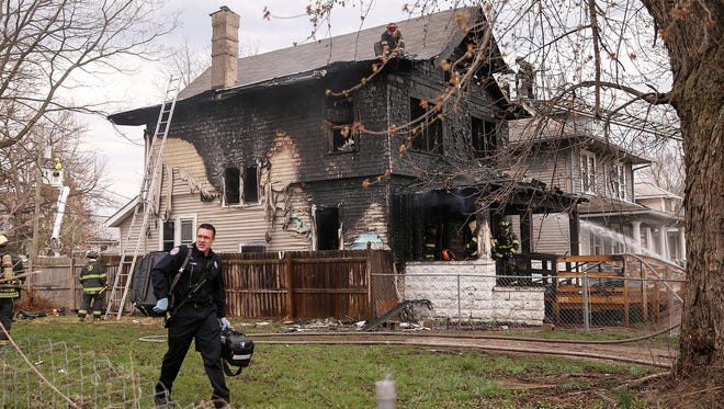 Indianapolis firefighters finish dousing a blaze in the 600 block of Udell Street in Indianapolis, Thursday, March 30, 2017. A grandmother, her daughter and three grandchildren safely escaped the home. The grandmother jumped from the roof of the back porch, and the mother and youngest two children went through the front door. A 20-year-old male, who is a quadriplegic. escaped with the help of a neighbor.