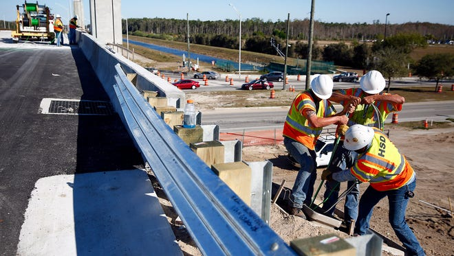 Employees of Highway Safety Devices work on wiring for the direct-connect road in February 2015 at Southwest Florida International Airport in Fort Myers.