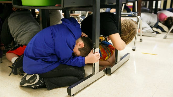 Third-grade students in Jill McAllister's class at Englewood Elementary School crawl under their desks and cover their head as they practice an earthquake drill for the Great Oregon ShakeOut on Thursday, Oct. 19, 2017. The drill was scheduled for 10:19 a.m. across the state, and students were instructed to stay in the covered position for two minutes before evacuating the building.