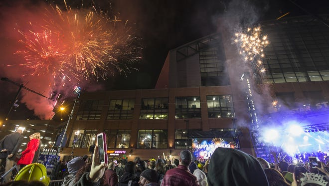 Fireworks go off near Banker's Life Fieldhouse as the clock strikes midnight during New Year's Eve on Georgia Street, downtown Indianapolis, Saturday, Dec. 31, 2016.