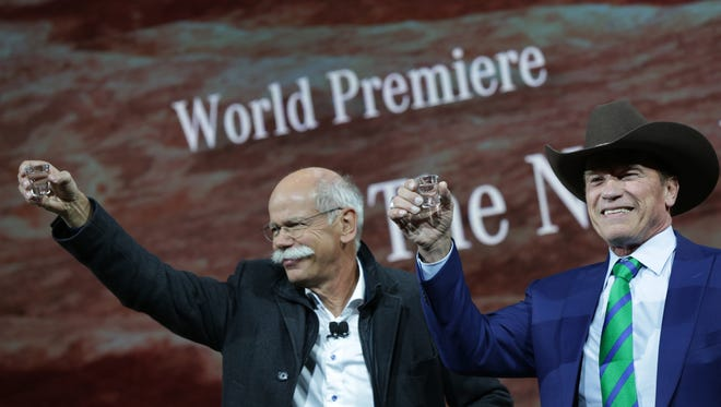 Daimler AG CEO, Dieter Zetsche, left is joined by Arnold Schwarzenegger for a toast during the unveiling of the updated Mercedes-Benz G-Class during the North American International Auto Show at the Michigan Theatre in Detroit Sunday, January 14, 2018. Schwarzenegger gifted a cowboy hat to Zetsche.