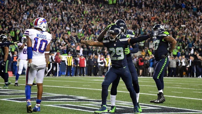 Seattle Seahawks safety Earl Thomas (29) celebrates with safety Kelcie McCray (33) after a Buffalo Bills incomplete pass on fourth down with 13 seconds left as Bills receiver Robert Woods (10) reacts during a NFL football game at CenturyLink Field.