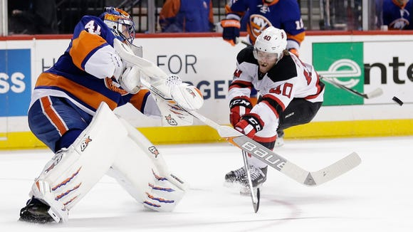Islanders goalie Jaroslav Halak (41) shoots the puck past the Devils' Blake Coleman (40) during the first period of a game Friday, March 31, 2017, in New York.