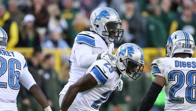 Lions cornerback Crezdon Butler, center front, and Ezekiel Ansah, center, celebrate after Butler broke up the Packers' two-point conversion attempt in the fourth quarter at Lambeau Field on Sunday.
