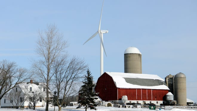 A Shirley Wind turbine dominates the sky over a farm on Wisconsin 96 west of Denmark on Jan. 31, 2013.