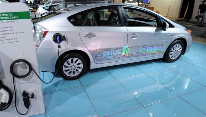 Toyota Prius plug-in hybrid car with model of a home charging station on display during the second press preview day at the 2012 North American International Auto Show