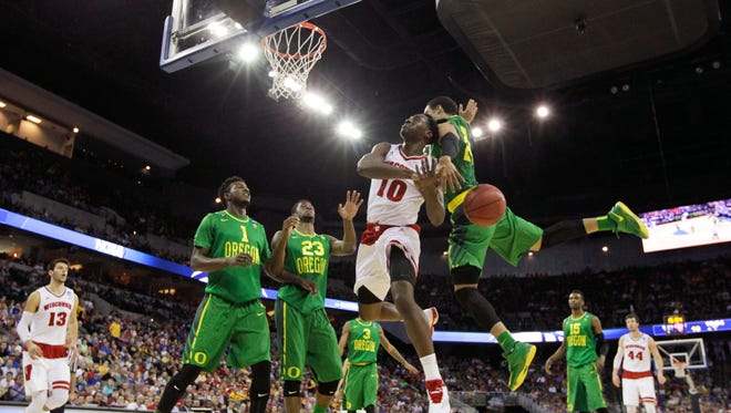 Wisconsin forward Nigel Hayes (10) is fouled by Oregon forward Dillon Brooks while driving to the basket during the first half of an NCAA college basketball tournament Round of 32 game, Sunday, March 22, 2015, in Omaha, Neb.