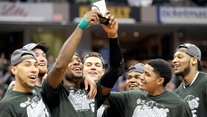 From left, Denzel Valentine, Matt Costello, Branden Dawson, Gavin Schilling, Alvin Ellis, Gary Harris and Adreian Payne celebrate MSU's 2014 Big Ten tournament championship.,