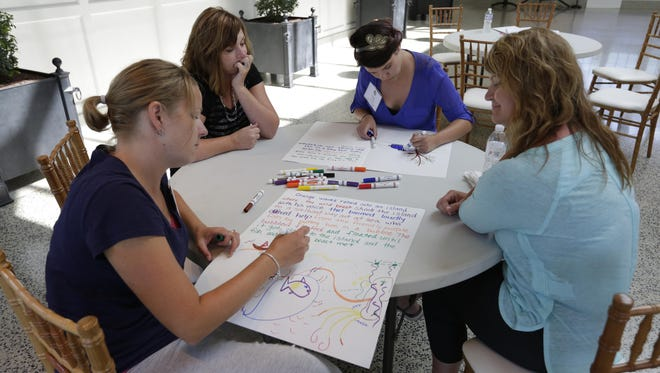Veronica Haag of Waukesha and Tina Ruckdashel of UW-Oshkosh Headstart to work on their story project with Tina Johnson of Mayville and Lisa Kortbein of UW-Oshkosh Headstart during the ArtsCore conference held at the Paine Art Center and Gardens on Monday August 10, 2015.