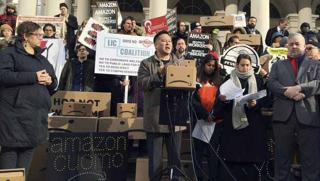 State Assemblyman Ron Kim, center, speaks at a rally opposing New York's deal with Amazon, on the steps of New York's City Hall, Dec. 12, 2018.