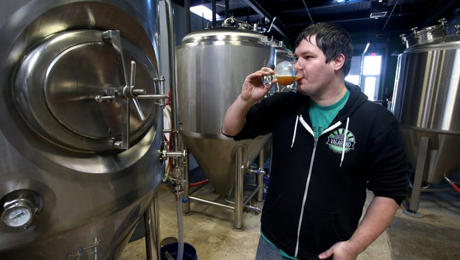 James Cardwell, co-owner and brewer at Vagabond Brewing, tests a batch of Attack Owl IPA on Tuesday.