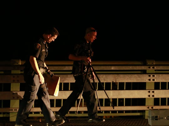 Ithaca police officers gather evidence Wednesday night on the west sidewalk of the Stewart Avenue bridge over Cascadilla Creek.