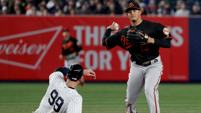Baltimore Orioles shortstop Manny Machado (13) throws to first to complete a double play as New York Yankees' Aaron Judge (99) slides after being forced during the third inning of a baseball game Friday, April 6, 2018, in New York. Didi Gregorius was out at first.